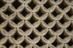Een wit concreet rooster van cirkels met een ruit binnen op een zwarte achtergrond royalty-vrije stock afbeelding