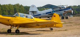 Een wit en een geel historisch klein vliegtuig op het vliegveld van het zweefvliegtuigvliegveld van Wilsche dichtbij Gifhorn stock afbeeldingen