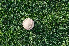 Een wit gebruikt honkbal op het verse groene gras Stock Foto