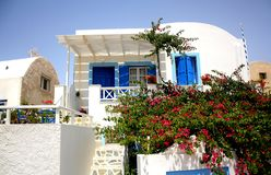 Een wit huis met blauwe geschilderde deuren en raamkozijnen en struik met bloemen op de voorscène in Santorini-Eiland royalty-vrije stock afbeeldingen