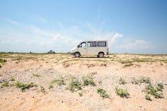 Een witte auto op de horizontribunes alleen op een woestijngebied in de middag royalty-vrije stock foto's