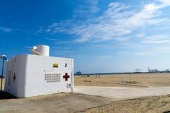 Een witte concrete badmeesterpost en een medisch centrum met rood kruis op groot strand in Valencia, Spanje Stock Foto's