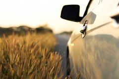 Een Witte die auto op de kant van de weg met de achtergrond van het onduidelijk beeldgebied wordt geparkeerd stock foto's