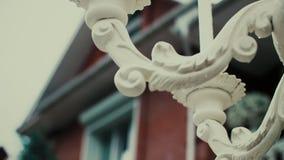 Een witte die fontein met mooie gravures wordt verfraaid bevindt zich tegen een rood baksteenbuitenhuis stock videobeelden