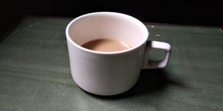 Een witte die kop half met thee wordt gevuld wordt geplaatst op de lijst royalty-vrije stock foto's