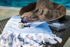 Een witte en blauwe Turkse handdoek, zonnebril, bikini en strohoed op rotanlanterfanter met blauw zwembad als achtergrond Stock Fotografie