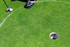 Een witte golfbal dichtbij het gat Stock Foto