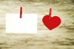 Een witte kaart en een rood hart die op een koord hangen, dat met rode gespen wordt vastgemaakt stock afbeelding