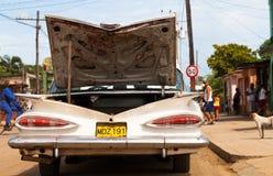 Een witte klassieke die auto op de weg wordt geparkeerd Stock Foto's