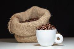 Een witte koffiemok met koffiebonen binnen en een koffiezak op witte lijst en zwarte achtergrond royalty-vrije stock afbeeldingen