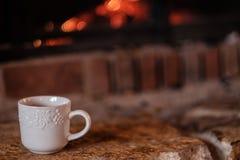 Een witte koffiemok op de haard stock afbeelding