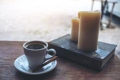 Een witte kop hete koffie met boek en kaarsen op uitstekende houten lijst Stock Afbeeldingen