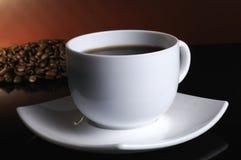 Een witte kop koffie en koffiebonen stock afbeeldingen
