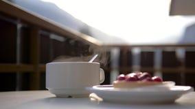 Een witte kop van hete drank en een plaat met dessert bij de koffie stock video