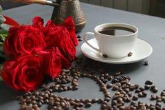 Een witte Kop van koffie en een boeket van rode rozen op de lijst Verspreide koffiebonen in de vorm van een hart royalty-vrije stock foto