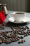 Een witte Kop van koffie en een boeket van rode rozen op de lijst Verspreide koffiebonen in de vorm van een hart stock foto's