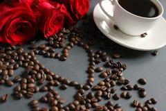 Een witte Kop van koffie en een boeket van rode rozen op de lijst Verspreide koffiebonen in de vorm van een hart royalty-vrije stock fotografie