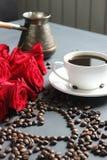 Een witte Kop van koffie en een boeket van rode rozen op de lijst Verspreide koffiebonen in de vorm van een hart royalty-vrije stock foto's