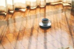 Een witte mok hete koffie op houten vloer door het gordijn stock afbeeldingen