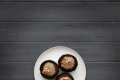 Een witte plaat met 3 cakes van de chocoladefee op een verontruste houten achtergrond stock fotografie