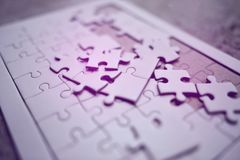Een witte puzzel wordt geplaatst op het stock foto