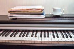 Een witte schotel en een kop thee op de hoofdkaas openden piano stock fotografie