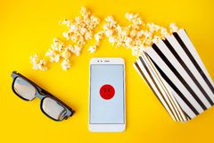 Een witte smartphone met smilies op het scherm, 3d glazen, een zwart-wit gestreept document vakje en een verspreide popcorn stock foto's