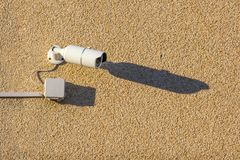 Een witte straatvideocamera met kabel hangt op een concrete muur royalty-vrije stock afbeelding