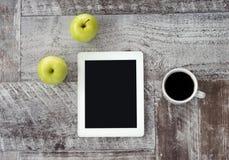 Een witte tablet met een kop koffie en groene appelen ligt op de lijst royalty-vrije stock afbeeldingen