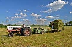 Een Witte tractor die een pers en een rek trekken Royalty-vrije Stock Foto's