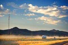 Een witte vrachtwagen op een stoffige snelweg Op de achtergrond zijn donkere bruine heuvels en een donkerblauwe hemel met pluizig Royalty-vrije Stock Afbeeldingen