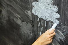 Een wolk en een regen met krijt op een bord wordt getrokken dat Stock Fotografie