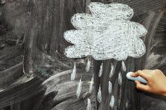 Een wolk en een regen met krijt op een bord wordt getrokken dat Royalty-vrije Stock Afbeeldingen