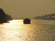 Een woonboot die tijdens zonsondergang bij Alleppy-Binnenwateren varen, Kerala, India stock foto's