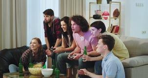 In een woonkamer heeft een groot bedrijf van multi etnische vrienden samen een funttijd in een videospelletje voor TV stock video