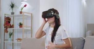 In een woonkamer op de bank maakte indruk een geconcentreerde mooie vrouw zeer op zij gebruikend een virtuele werkelijkheidsglaze stock footage