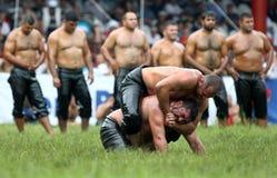 Een worstelaar plaatst zijn tegenstander binnen in een hoofdslot tijdens een woeste slag bij het de Olie van Kirkpinar Turkse het Stock Afbeeldingen