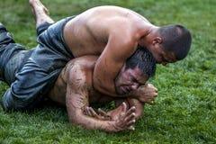 Een worstelaar wordt gedwongen in voorlegging door zijn tegenstander bij het de Olie van Kemer Turkse het Worstelen Festival, Kem stock afbeelding