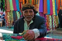 Een yemeni oude mens betaalt na gewinkeld bij de stoffenopslag in de zoute markt van de Oude Stad van Sana'a, Yemen, tulband, sja stock fotografie
