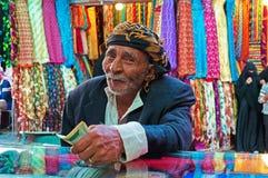 Een yemeni oude mens betaalt na gewinkeld bij de stoffenopslag in de zoute markt van de Oude Stad van Sana'a, Yemen, tulband, sja royalty-vrije stock foto's
