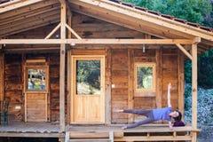 Een yoga van vrouwenpraktijken op de portiek van een oud blokhuis royalty-vrije stock foto's