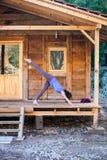 Een yoga van vrouwenpraktijken op de portiek van een oud blokhuis stock afbeeldingen