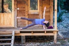 Een yoga van vrouwenpraktijken op de portiek van een oud blokhuis stock afbeelding