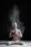 Een yogaleraar zit in een sukhasana op een zwarte achtergrond Stock Afbeelding
