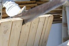 Een zaag snijdt houten raad, wat in de hand van een mens, het concept reparatie, bouw, natuurlijke materialen is royalty-vrije stock fotografie