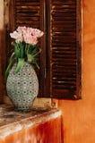 Een zacht geconcentreerd boeket van bloemen in een oude vaas op een venster sil royalty-vrije stock afbeeldingen