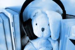 Een zacht stuk speelgoed konijntje die te grote hoofdtelefoons dragen Omringd door boeken royalty-vrije stock fotografie