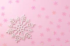 Een zachte magische witte sneeuwvlok van een sprookje op een lichtrose achtergrond royalty-vrije stock foto