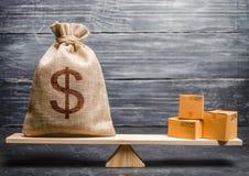 Een zak geld en een bos van dozen op de schalen Conceptuele handelsbalans tussen landen en vakbonden, handel en uitwisseling stock foto