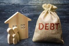 Een zak geld met de woordschuld en de familie die zich dichtbij het huis bevinden Het concept schuld voor huisvesting hypotheek O stock fotografie